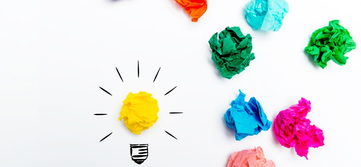 Crumpled paper light bulb over white background, surrounded by colorful Crumpled paper